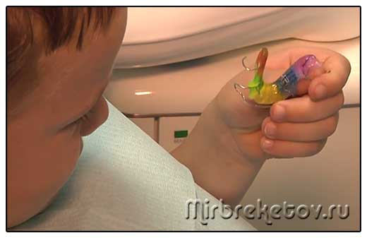 ребенок держит в руках ортодонтическую пластинку
